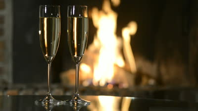 stock-footage-two-champagne-glasses-in-front-of-fireplace